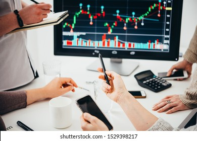 A group of colleagues discussing recent stock exchange trends pointing to the stock exchange screen showing trading graphics