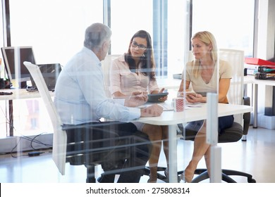 Group of colleagues meeting around a table in an office