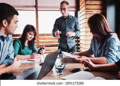 Group of colleagues in the office doing brainstorming - Businessman holding a meeting with employees - Millennials launching a startup and discussing a project in the office