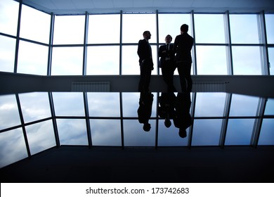 Group of colleagues standing against window in office and speaking