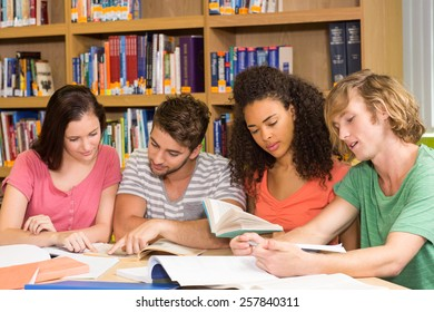 Group of college students doing homework in the library