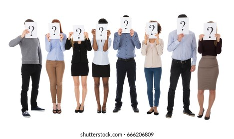 Group Of College Students Hiding Behind Question Mark Sign Against White Background