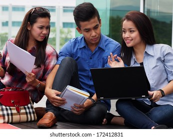 A group of college students studying outside campus building