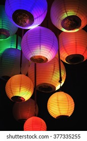 Group of colored paper lanterns glowing in the dark