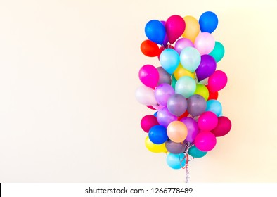 Group of colorful balloons on pastel color background.