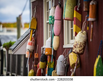 Group of colorful buoys hanging on side of boat shed.