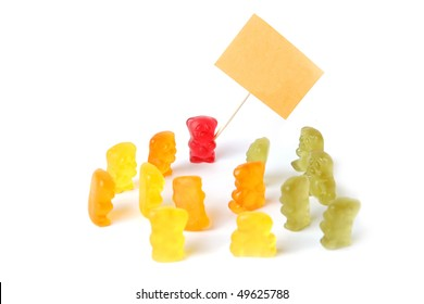 Group of colorful gummy bears holding an empty sign on white background