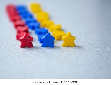Group of colorful meeples of teams isolated on gray background. Small figures of man. Board games concept. Army and business. Goals of company.