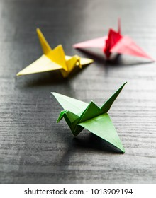 A group of colorful origami cranes on darkwooden background with copy space