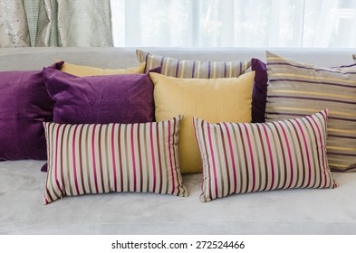 group of colorful pillows on sofa in living room at home