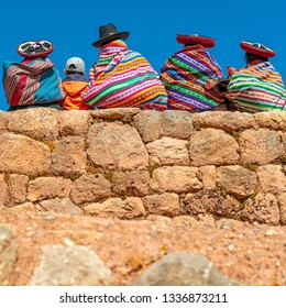 A group of colorful Quechua indigenous women with a 21st century boy sitting on an Inca wall in the archaeological site of Chinchero, Cusco Province, Peru.