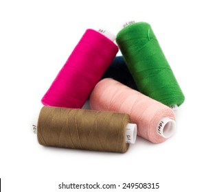 Group of colorful sewing threads isolated on white background