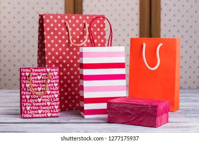 Group of colorful shopping bags. Set of different gift packets with handles and pink gift box. Holiday purchasing concept.