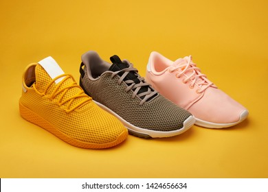 Group of colorful sport shoes stand on orange background