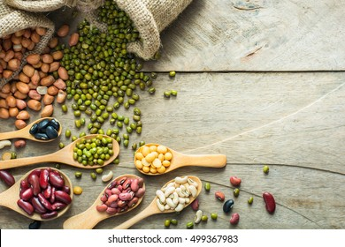 Group of colorful various beans or lentils and whole grains seeds or cereal in hemp sack and empty blackboard on wood table background. mung bean, groundnut, blackbean, red kidney bean, soybean