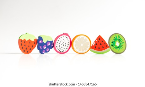 Group of colourful eraser toy fruit. Concept of healthy fruit. Isolated on white. Copy space.