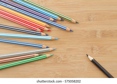 Group of colourful stripe color pencil on one side with black plain colour pencil on another side. Concept of difference,discrimination,leadership,illness,disability,fight,strong,confident.