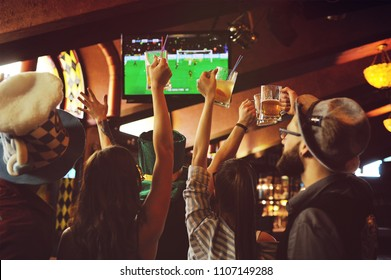 group or company of friends - young guys and girls holding glasses of beer, watching football, laughing and smiling at the bar during the Oktoberfest festival