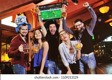group or company of friends - young guys and girls holding glasses of beer, watching football, laughing and smiling at the bar during the festival