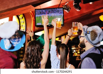 group or company of young people friends in Bavarian caps - guys and girls watching football on TV in a sports bar holding glasses with beer. Celebration of the Oktoberfest festival