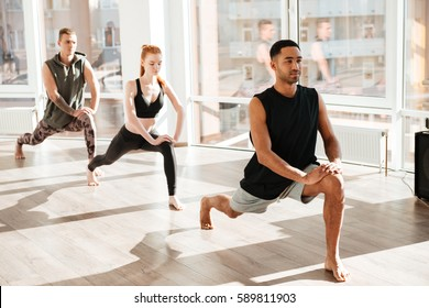Group of concentrated barefoot young people doing yoga exercises in studio