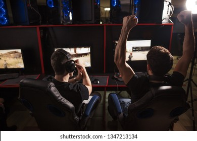 group of concentrated guys in headphones enjoying online video game on powerful computers of gaming centre, rear view.
