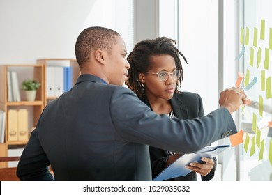 Group of concentrated white collar workers standing at glass board and reading sticky notes while having working meeting in spacious boardroom