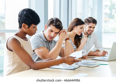 Group of concentrated young business people sitting and working with documents in office