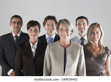 Group of confidence businesspeople smiling against gray background