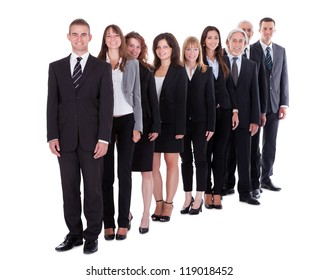 Group of confident business people in a team or partnership standing in a staggered row smiling at the camera isolated on white