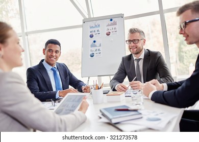 Group of confident employees listening to their colleague at meeting in office