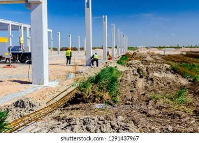Group of construction workers with safety vests and yellow helmets, are assembly vertical concrete pillar to foundation on new edifice, at building site.