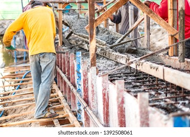 Group of construction workers spreading poured concrete for bridge building at construction site.