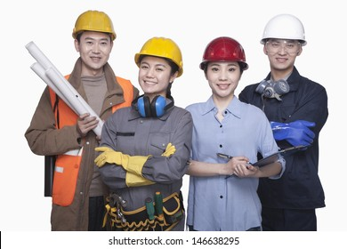 Group of construction workers standing against white background, smiling, portrait