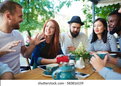 Group of contemporary young people having conversation at hangout