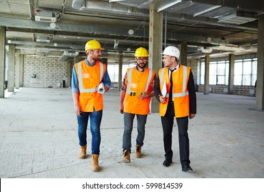 Group of contractors walking down concrete floor of unfinished construction and having talk
