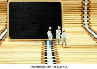 Group of cook are discussion for creating menu. Empty space on blackboard for writing menu or text.