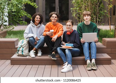Group of cool joyful students sitting and happily looking in camera while spending time together in courtyard of university