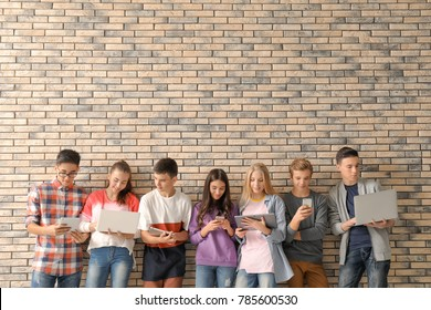 Group of cool teenagers with modern devices near brick wall