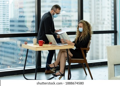 Group of corporate colleagues wearing protective medical face mask for health, in formal suit, discussing of work in the modern office. health, businesspeople and office concept