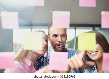 Group of corporate people brainstorming  on new project with many sticky notes on window