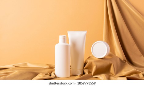 Group of cosmetics tubes bottles abstract podium yellow background draped cloth.