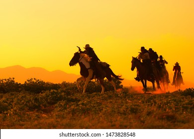 Group of Cowboy riding horse.Silhouette Cowboy on horseback.Cowboy  riding horse at sunset or sunrise time.