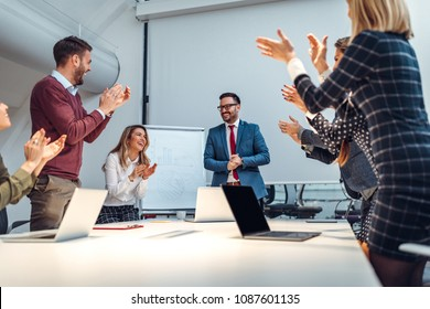 Group of coworkers clapping in a boardroom