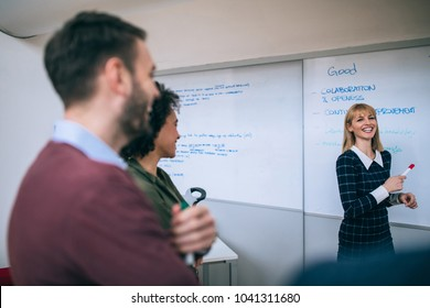 Group of coworkers during a meeting , standing in front of a white board