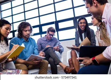 Group of coworkers with folders interacting in the office