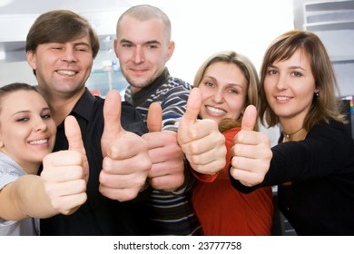 Group of coworkers lifting thumbs up