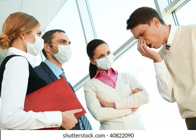 Group of co-workers in protective masks looking strictly at sneezing man