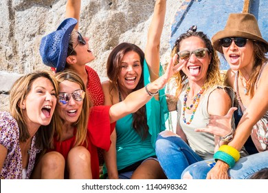 group of crazy nice beautiful caucasian girls outdoor under the summer sun doing a party all together. people having fun iall together oncept lifestyle. shout and laugh full of joyful women