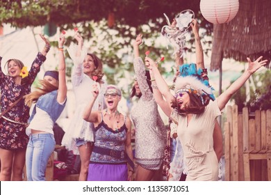 group of crazy women mixed ages from young to old having fun and dancing all together in a hippy style event. celebrating group people concept with colored clothes and happiness